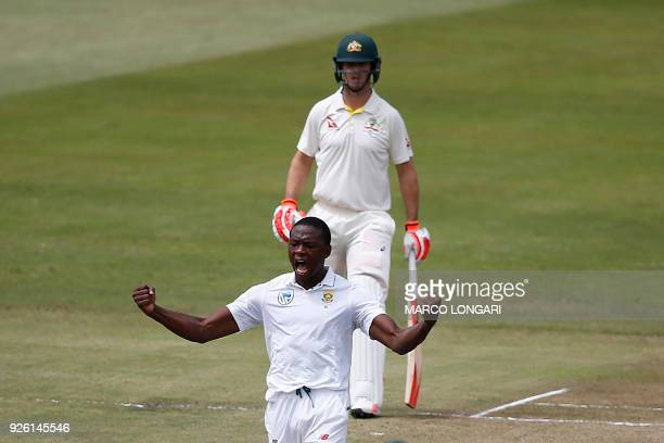 South African bowler Kagiso Rabada celebrates after taking the wicket of unseen Australian batsman Tim Paine during play on the second day two of the...