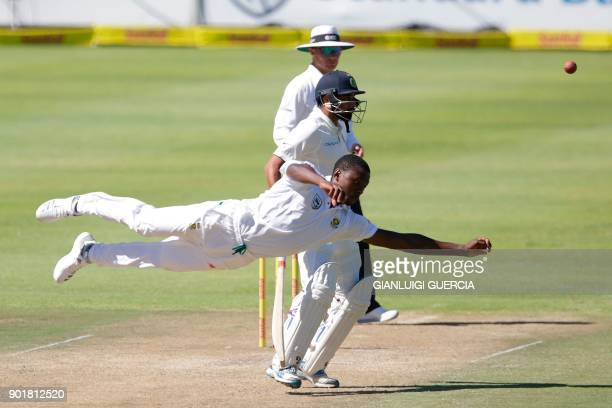 TOPSHOT South African bowler Kagiso Rabada dives as he tries to field on his own bowling during the second day of the first Test cricket match...