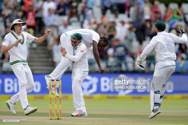 South African bowler Kagiso Rabada is lifted by South African fielder Dean Elgar as he celebrates with teammates the dismissal of Indian batsman...