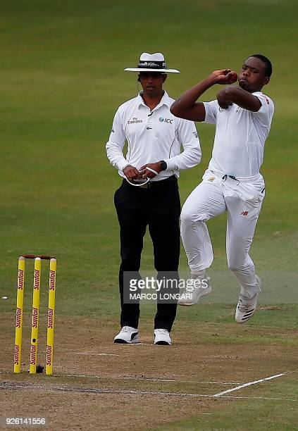 South African bowler Kagiso Rabada is watched by umpire Kumar Dharmasena as he delivers a ball during play on the second day two of the first Test...