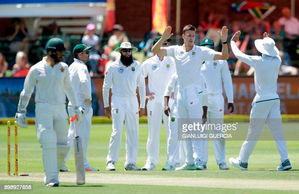 South African bowler Morne Morkel celebrates with teammmates after the dismissal of Zimbabwean batsman Ryan Burl during the second day of the day...