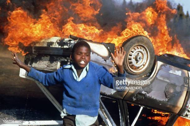 South African boy dances, 10 July 1985 in Duduza township, around a car of a suspected police informer being burnt during an anti-apartheid riot,...