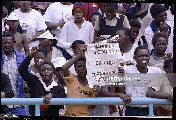 A South African boys holds up a sign stating Mandela is coming Join ANC[African National Congress] Forward to Victory at a celebration for the...