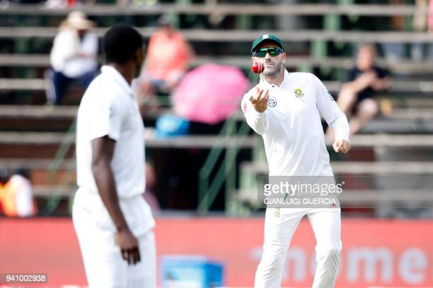 South African Captain Faf du Plessis passes the ball to South African bowler Kagiso Rabada on the fourth day of the fourth Test cricket match between...