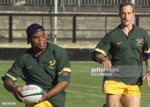 South African centre Kaya Malotana passes the ball watched by wing Stefan Terblanche during a training session at the Goldenacre rugby stadium in...