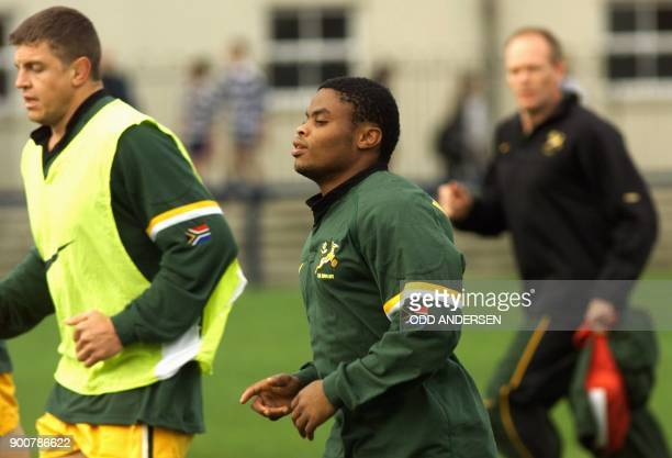 South African centre Kaya Malotana with teammate Krynauw Otto runs under the watchfull eye of team physiotherapist Wayne Diesel during a training...