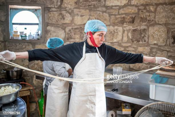 South African cheesemaker Marietjie Crowther pulls pasta filante to make string cheese in Clarens, on July 13, 2020 in the small lab-turned-hut of...