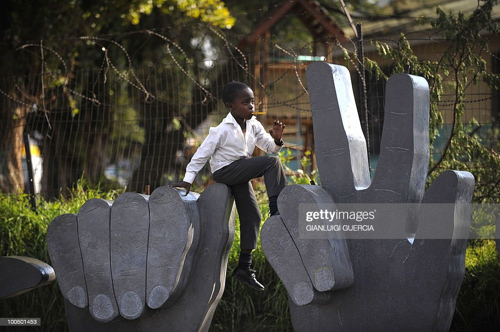 A South African child plays on a sculpture on May 21, 2010 during the official celebration marking 20 days ahead of the FIFA WC2010 kick off on Vilakazi street in Soweto, South Africa. South Africa will host the FIFA World Cup from the 11 of June to the 11 of July, 2010.