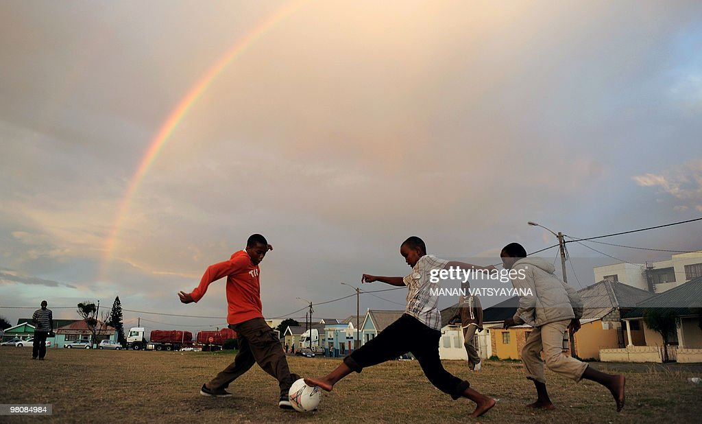 South African children play football in their neighbourhood as a rainbow appears in the sky in East London on May 8, 2009. South Africa will host the 2010 FIFA World Cup scheduled to take place between June 11 - July 11 2010.