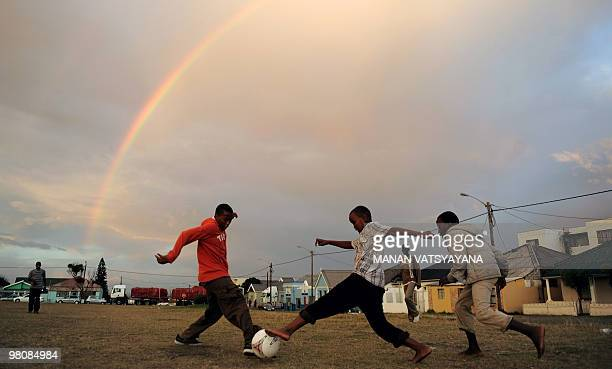 South African children play football in their neighbourhood as a rainbow appears in the sky in East London on May 8 2009 South Africa will host the...