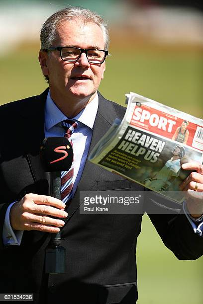 South African commentator displays the backpage of The West Australian newspaper while doing a piece to camera before start of play during day five...