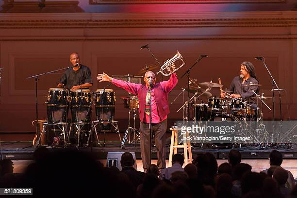 South African composer bandleader and musician Hugh Masekela plays fluegelhorn as he leads his band onstage at the 'Twenty Years of Freedom' concert...