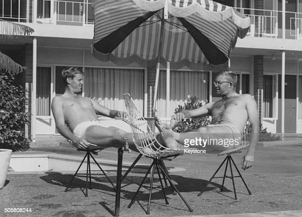 South African cricket players Graeme Pollock and Eddie Barlow relaxing around the pool of their motel after making a record breaking stand as batsmen...