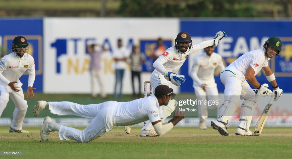 South African cricketer Aiden Markram (4L) and Sri Lankan wicket keeper Niroshan Dickwella (3L) look on as Sri Lankan cricketer Angelo Mathews takes a diving catch during the first day's play in the 1st Test cricket match between Sri Lanka and South Africa at Galle International cricket stadium, Galle, Sri Lanka on Thursday 12 July 2018