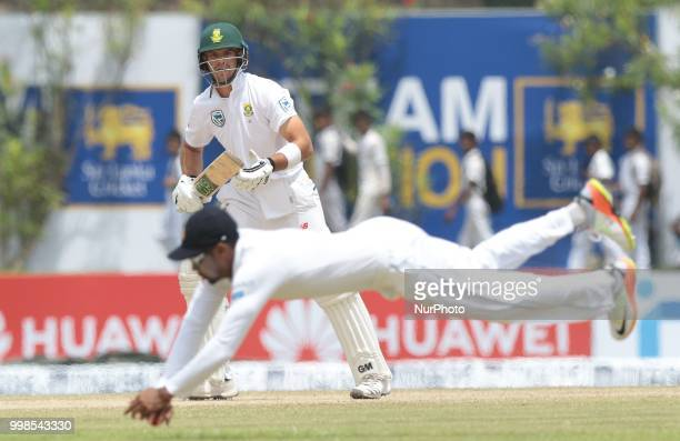 South African cricketer Aiden Markram looks on as Sri Lanka's Danushka Gunathilaka dives in to stop the ball during the 3rd day's play in the first...