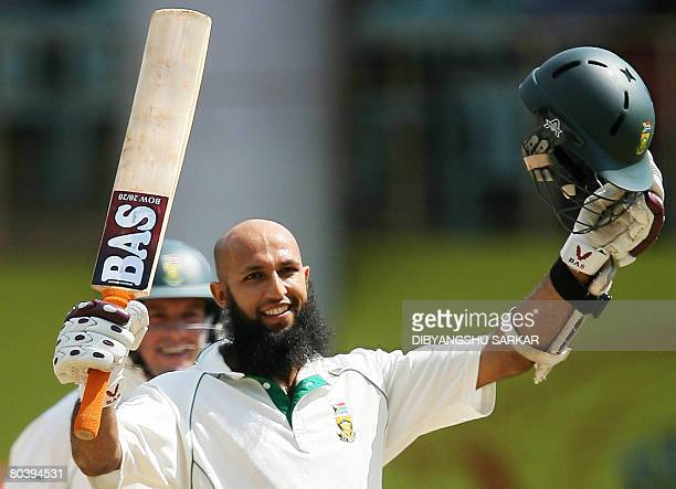 South African cricketer Hashim Amla celebrates scoring a century during the second day of the first Test match between India and South Africa at The...