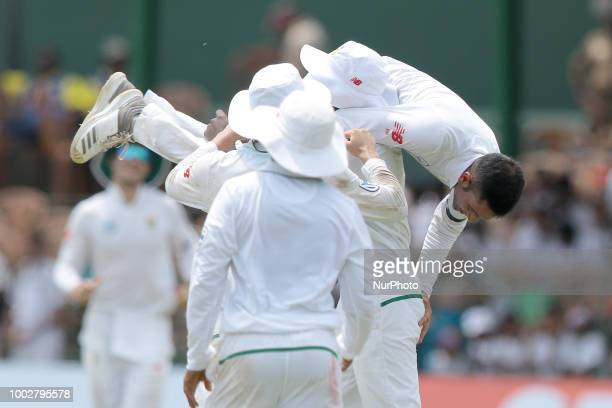 South African cricketer Keshav Maharaj is lifted up by Kagiso Rabada in celebration during the first day of the 2nd test cricket match between Sri...
