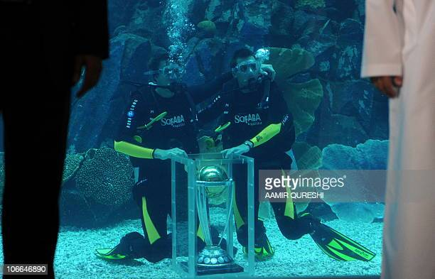 South African cricketer Morne Morkel and Dale Steyn pose underwater with the ICC World Cup trophy, during a ceremony at the Dubai Mall aquarium on...