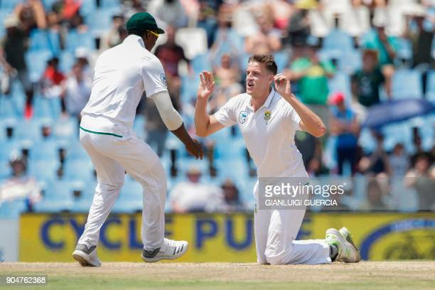 South African cricketer Morne Morkel celebrates with a teammate the dismissal of Indian batsman Lokesh Rahul during the second day of the second Test...