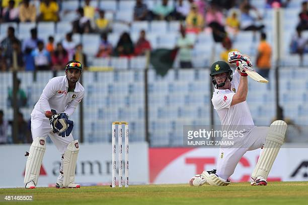 South African cricketer Simon Harmer plays a shot as Bangladesh wicketkeeper Litton Das looks on during the first day of the first Test match between...