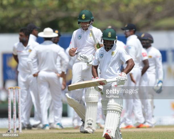 South African cricketer Temba Bavuma walks off as Sri Lankan cricket players celebrate during the 3rd day's play in the first Test cricket match...