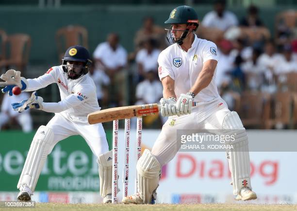 South African cricketer Theunis de Bruyn plays a shot as wicketkeeper Niroshan Dickwella looks on during the third day of their second Test match...