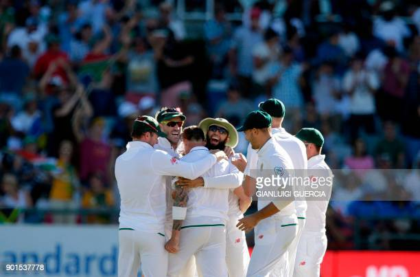 South African cricketers congratulate teammate Dale Steyn as he celebrates the dismissal of unseen Indian batsman Shikhar Dhawan during the first day...