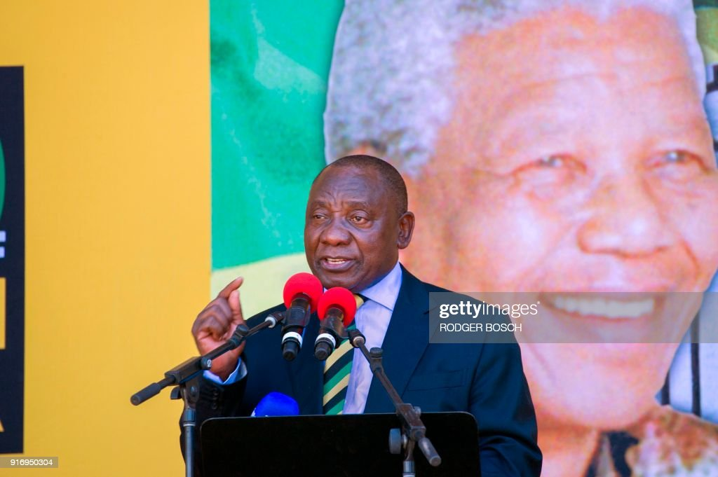 South African Deputy President and newly-elected president of the ruling African National Congress (ANC), Cyril Ramaphosa speaks during a rally on February 11, 2018 in Cape Town, from the same spot where exactly 28 years before, Nelson Mandela (on poster) had first addressed South Africans, after being released from a 27 year jail term. South Africa's president-in-waiting Cyril Ramaphosa admitted February 11 to 'disunity and discord' in the ruling ANC party as the deadlocked effort to oust scandal-tainted leader Jacob Zuma grinds on. With Zuma refusing a party request to resign, the African National Congress (ANC) top decision-making committee will meet on February 12. BOSCH