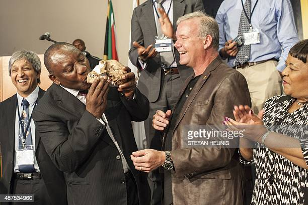 South African Deputy President Cyril Ramaphos kisses a replica of the skull of a Homo Naledi a newly discovered human ancestor during the unveiling...