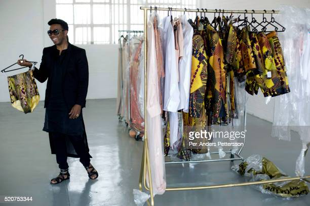 South African designer David Tlale shows a garment from his latest collection in his studio at Mercedes Benz Africa fashion week Africa on October 30...