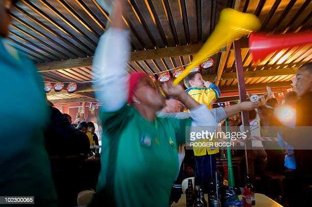 South African fans cheer their team's second goal at Mzoli's Tavern and Butchery in Gugulethu township some 20km from Cape Town the 2010 Football...