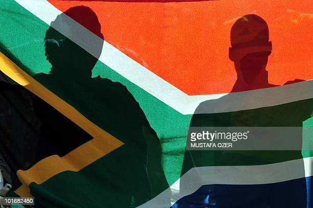 South African fans hold their national flag as Slovenia's national football team arrives at their hotel in Johannesburg on June 7 2010 ahead of the...