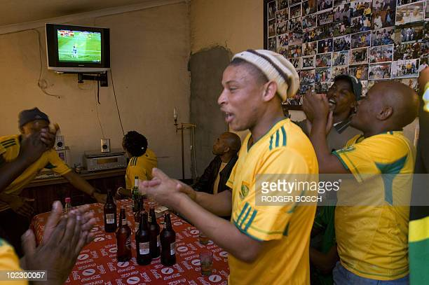 South African fans react as they watch at a taver in Gugulethu township some 20km from Cape Town the 2010 Football World Cup match between South...