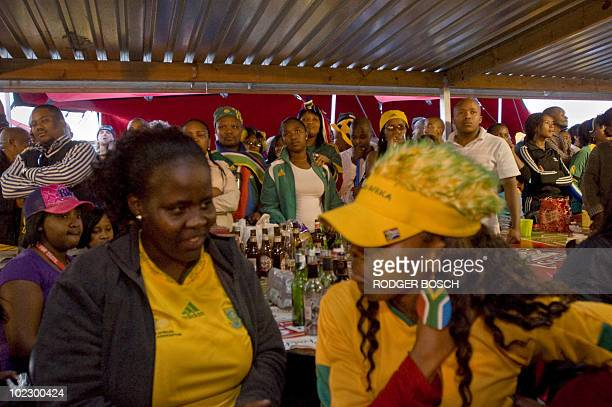 South African fans react as they watch at Mzoli's Tavern and Butchery in Gugulethu township some 20km from Cape Town the 2010 Football World Cup...