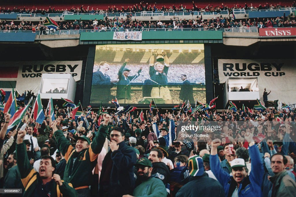 South African fans watch Francois Pienaar lift the trophy after South Africa defeated New Zealand in the Rugby World Cup final at Ellis Park, Johannesburg, 24th June 1995.