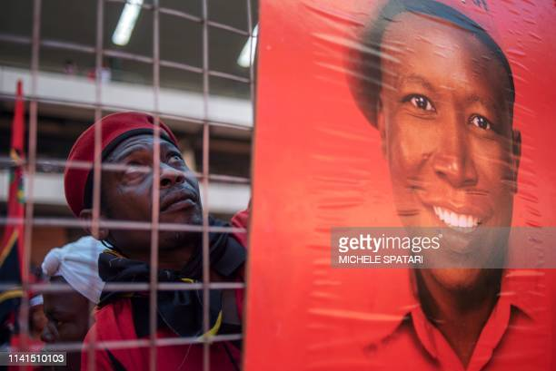 A South African farleft and opposition party Economic Freedom Fighters supporter hangs a banner depicting party leader Julius Malema during the final...