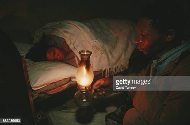 A South African farm worker brings a lamp to his wife's bedside at 6 am to wake her for her job just before he himself leaves home for the fields She...