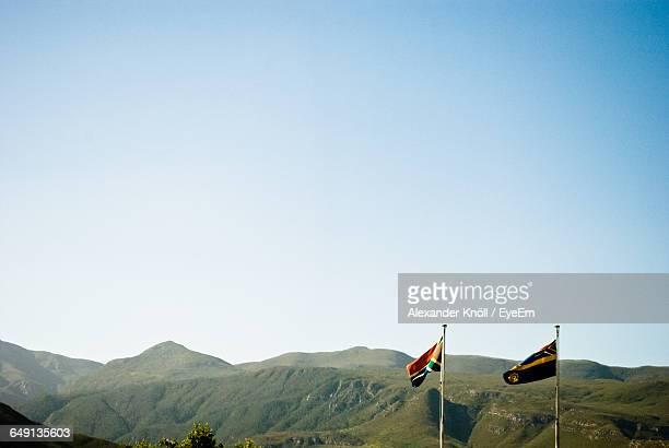 south african flag and mountains against clear sky on sunny day - south african flag stock photos and pictures
