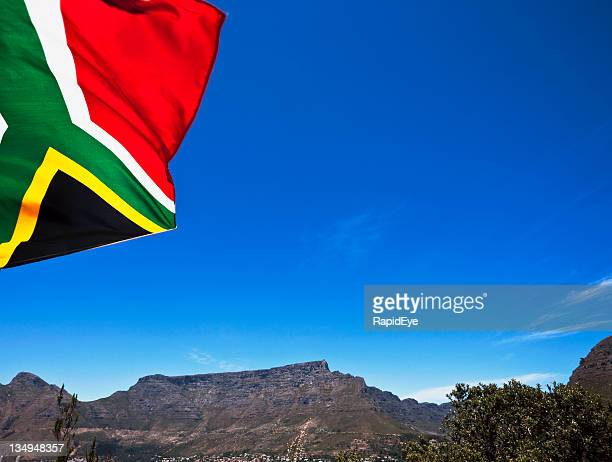 south african flag flies against table mountain backdrop - south africa stock pictures, royalty-free photos & images