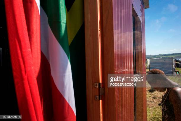 A South African flag hangs in a recently built shack of woman on a piece of land belonging to the Louiesenhof Wine Estate on August 08 in...