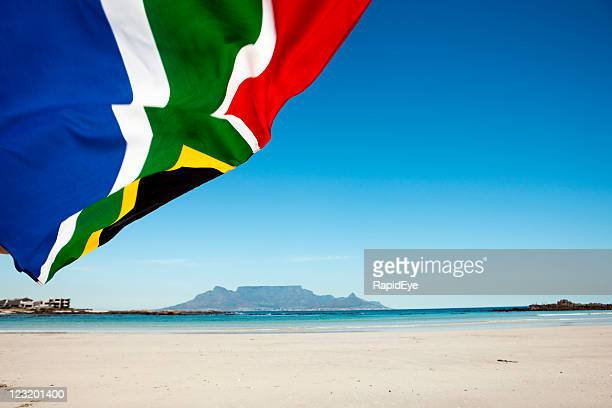 south african flag waves  in front of table mountain - south african flag stock photos and pictures