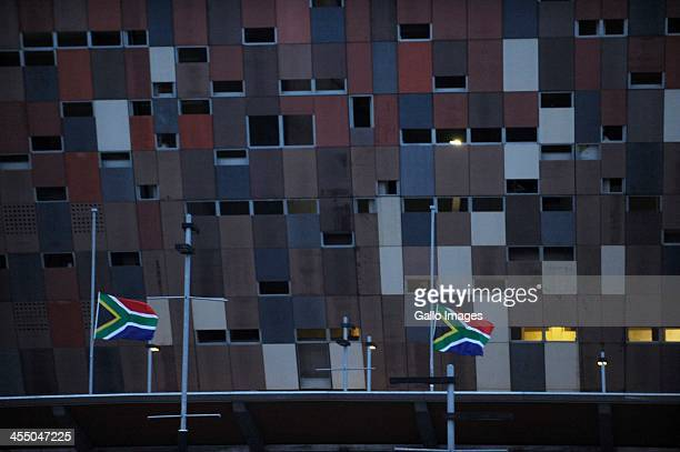 South African flags fly half mast during the official memorial service for former South African President Nelson Mandela at the FNB Stadium on...