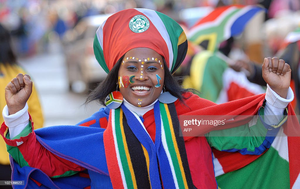 A South African football fan smiles along a street in Pretoria on June 16, 2010 just hours before the 2010 World Cup football match between South Africa and Uruguay. AFP PHOTO / Monirul Bhuiyan