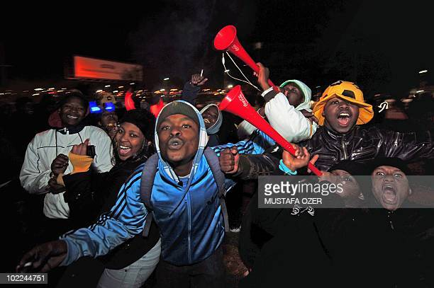 South African football fans blow vuvuzelas as they cheer on the country's team in Soweto outside Johannesburg on June 16 2010 while watching the...