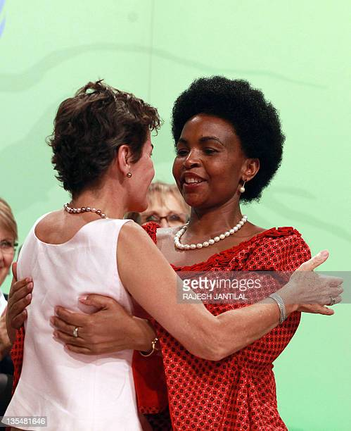 South African Foreign Affairs Minister and President of the 17th Conference of the Parties Maite Nkoana Mashabane gets a congratulatory hug from...