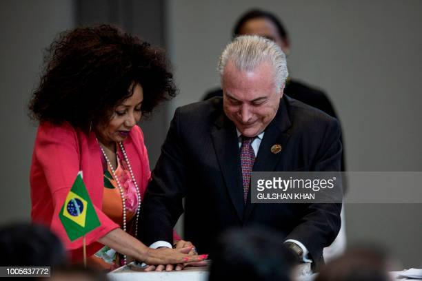 South African Foreign Minister Lindiwe Sisulu helps Brazil's President Michel Temer as he leaves a handprint in clay at the open session meetingthe...