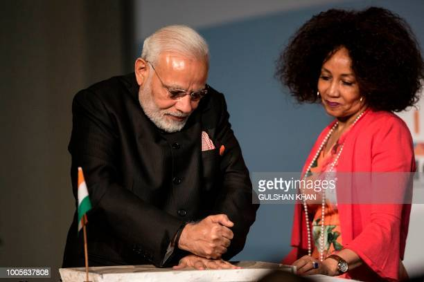 South African Foreign Minister Lindiwe Sisulu helps Indian Prime Minister Narendra Modi as he leaves a handprint in clay during the Open Session...