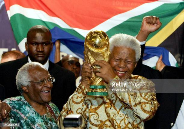 South African former President Nelson Mandela holds the Jules Rimet World cup beside Capetown Archbishop Desmond Tutu, 15 May 2004 at the FIFA...