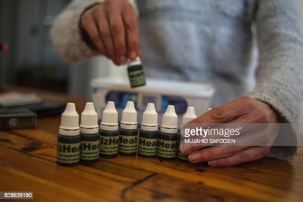 South African Gerd Bader affected by Multiple Sclerosis and who manufactures concentrated cannabis oil shows flacons with oil produced from his...