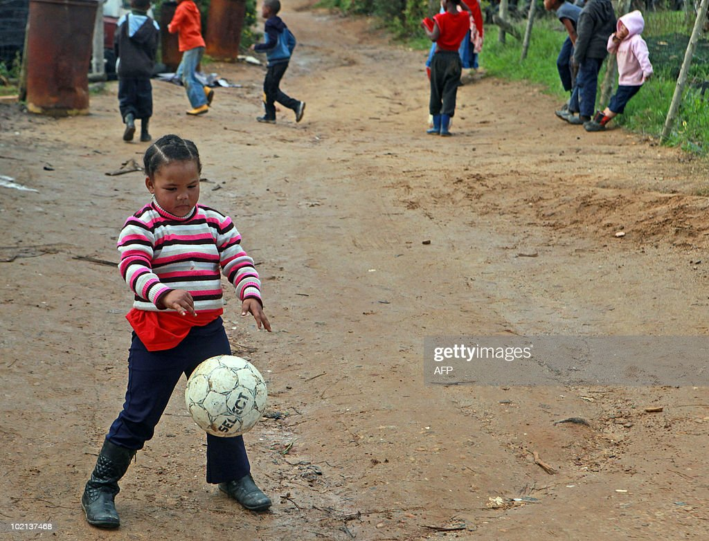 A South African girl plays football on a fruit farm in Stellenbosch, outside Cape Town, on June 16, 2010. South Africa celebrates the 34th anniversary of the Soweto student uprising today. The Bafana Bafana, the South African team, face Uruguay later today in their second match of the 2010 Football World Cup at Loftus in Pretoria. AFP PHOTO / Nardus Engelbrecht